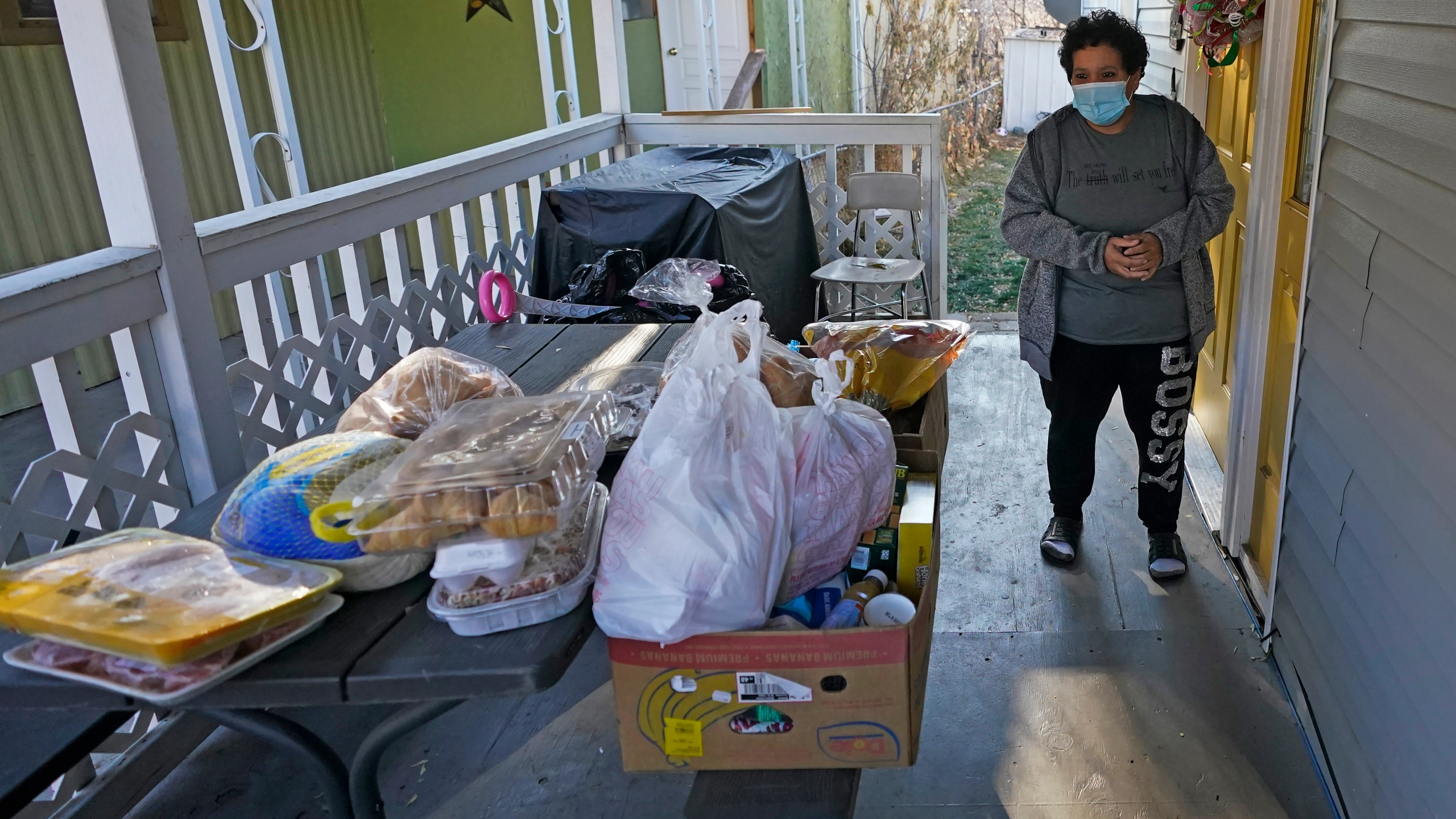Evelyn Maysonet looks at the food delivery from the Weber-Morgan Health Department Tuesday, Nov. 24, 2020, in Ogden, Utah. Maysonet has been isolating with her husband and son in their Ogden home since all three tested positive for COVID-19 over a week ago. None of them have been able to leave home to buy groceries so Maysonet said they were thrilled to receive the health department's delivery. (AP Photo/Rick Bowmer)