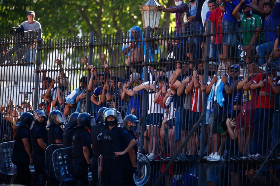 Mourning fans climb the fence of the presidential palace to get a glimpse of the casket carrying Diego Maradona's body in Buenos Aires, Argentina, on Nov. 26, 2020. (Marcos Brindicci / Associated Press)