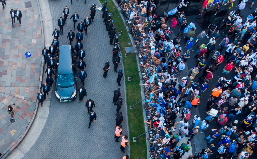 The hearse carrying the casket of Diego Maradona leaves the government house in Buenos Aires, Argentina, on Nov. 26, 2020. (Mario De Fina / Associated Press)