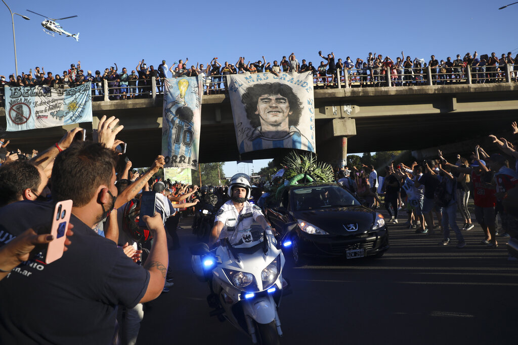 Mourning fans wave from an overpass at the caravan carrying the remains of Diego Maradona to his resting place in Buenos Aires, Argentina, Thursday, Nov. 26, 2020. (AP Photo/Rodrigo Abd)