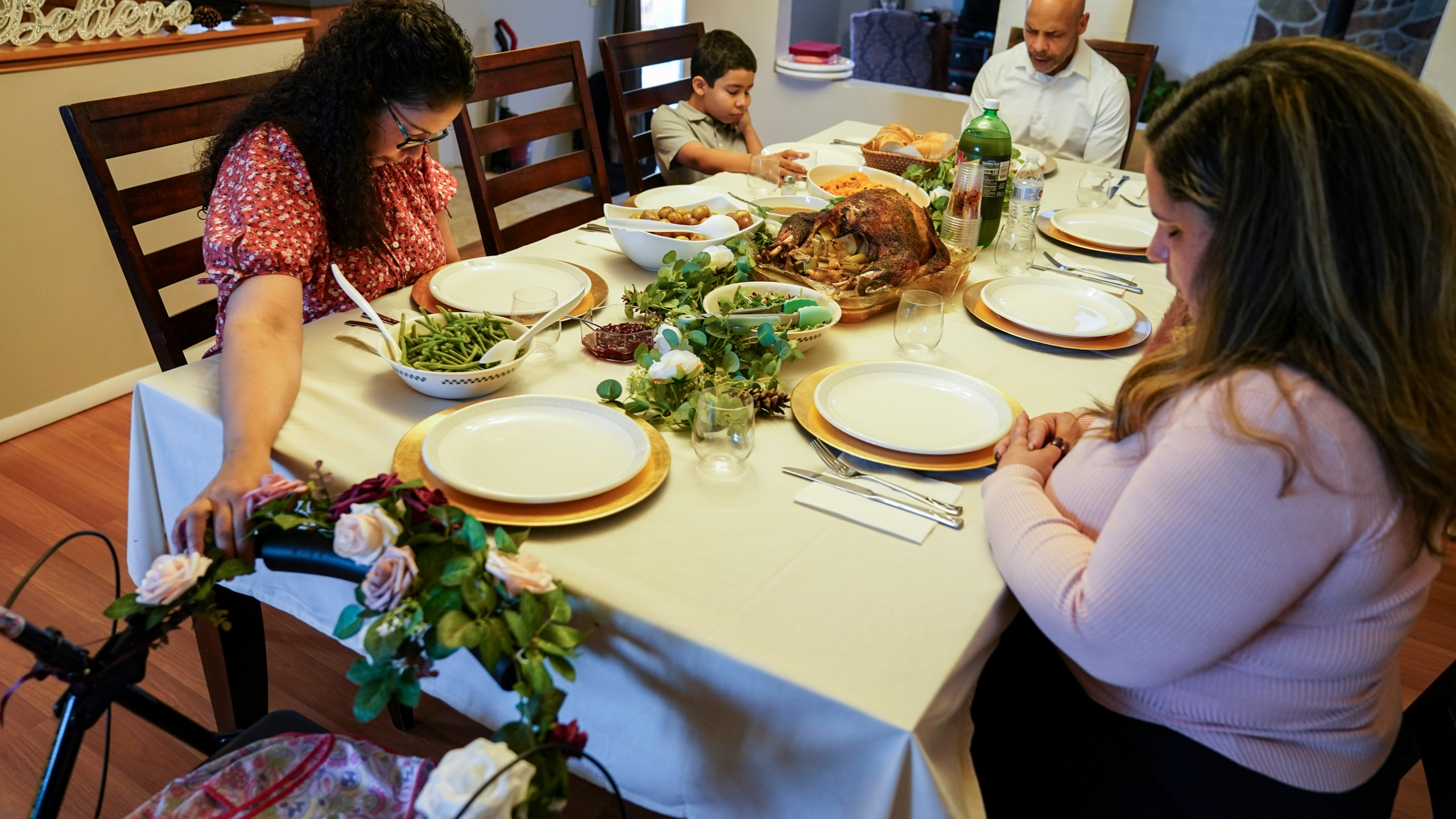 Vivian Zayas holds onto the walker once belonging to her recently deceased mother Ana Martinez while her family prays before Thanksgiving dinner on Nov. 26, 2020, in Deer Park, N.Y. Ana Martinez died at 78 on April 1 while recovering at a nursing home from a knee replacement. (John Minchillo / Associated Press)