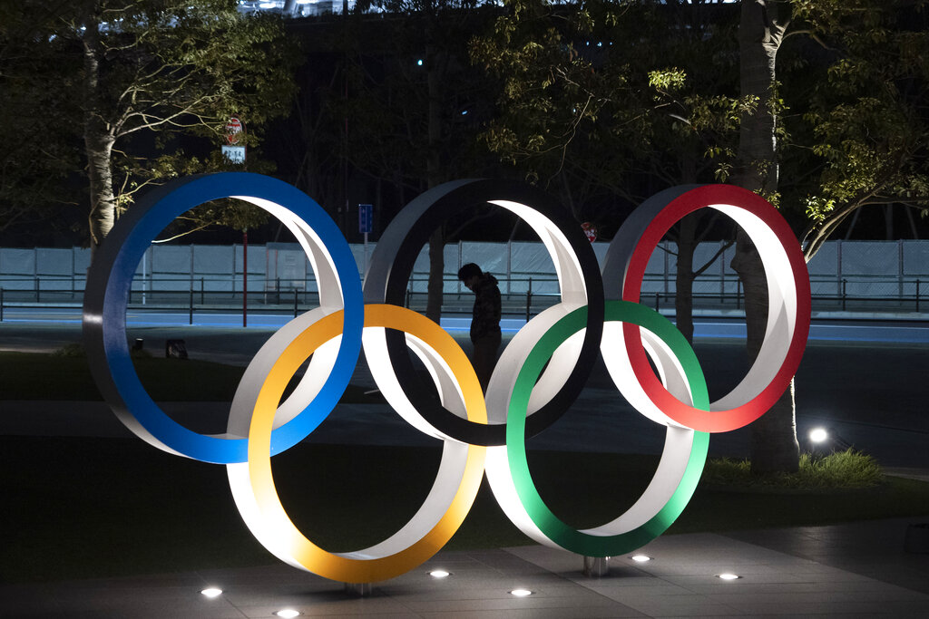In this March 24, 2020, file photo, a man is seen through the Olympic rings in front of the New National Stadium in Tokyo.