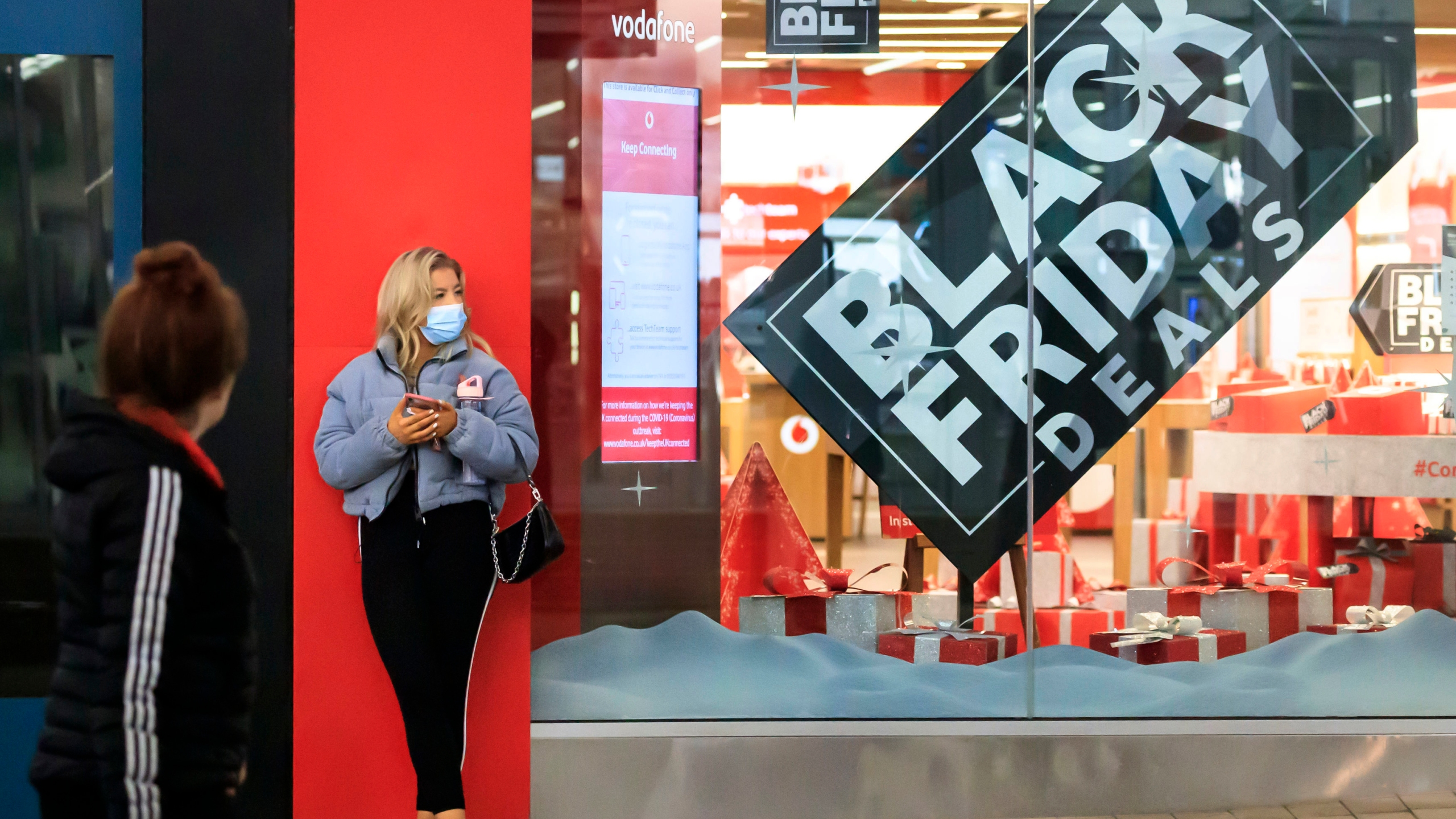 A woman next to a Black Friday poster in the window of a mobile phone store in Manchester city centre, England, although most stores remain closed Saturday Nov. 28, 2020. (Danny Lawson/PA via AP)