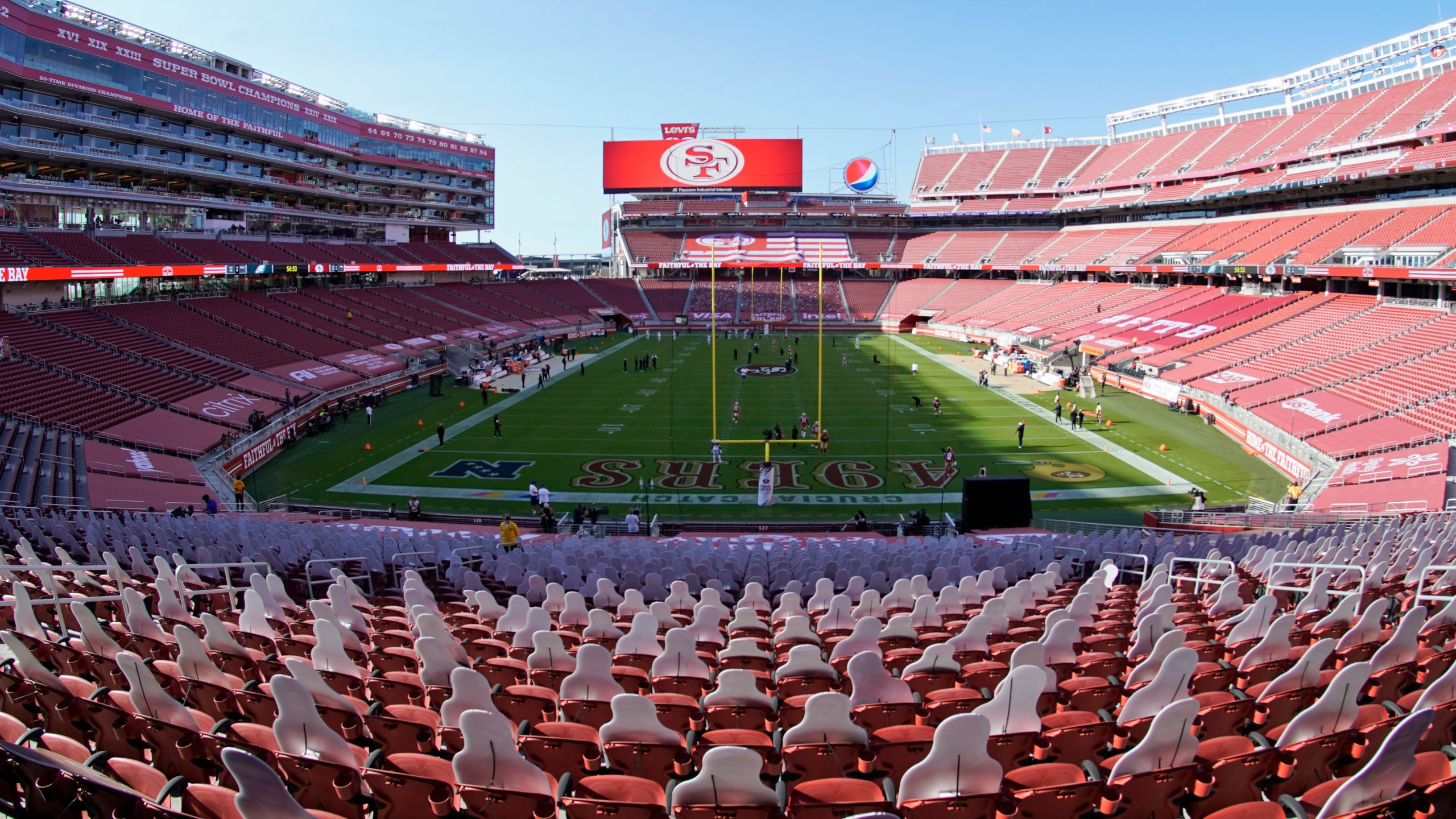 This Oct. 4, 2020, file photo, taken with a fisheye lens, shows an empty Levi's Stadium before an NFL football game between the San Francisco 49ers and the Philadelphia Eagles in Santa Clara, Calif. The 49ers and other teams may need to find a temporary new home after Santa Clara County on Nov. 28, 2020, banned all contact sports from holding games and practices for the next three weeks. County officials issued the directives in response to rising cases of the coronavirus in the area. The rules take effect Monday and will last for three weeks. (AP Photo/Tony Avelar, File)