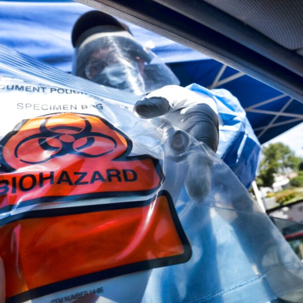 In this May 6, 2020 photo a medical worker hands a self administered coronavirus test to a patient at a drive through testing site in a parking lot in the Woodland Hills. (AP Photo/Richard Vogel, File)