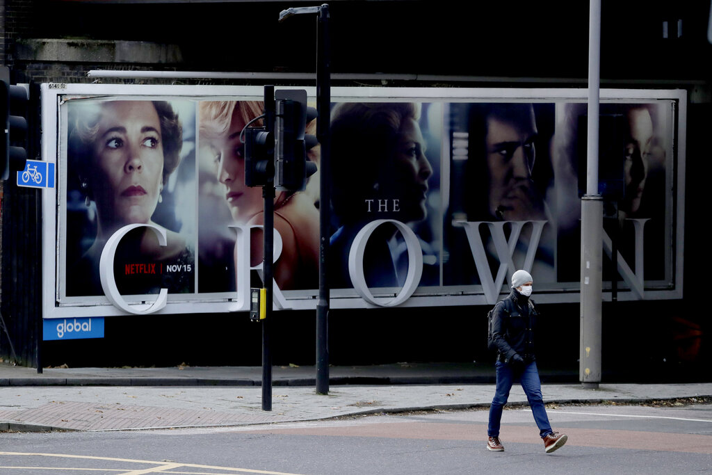 In this file photo dated Friday, Nov. 20, 2020, a man wearing a face mask walks past a billboard advertising 'The Crown' television series about Britain's Queen Elizabeth II and the royal family, during England's second coronavirus lockdown, in London. (AP Photo/Matt Dunham, FILE)
