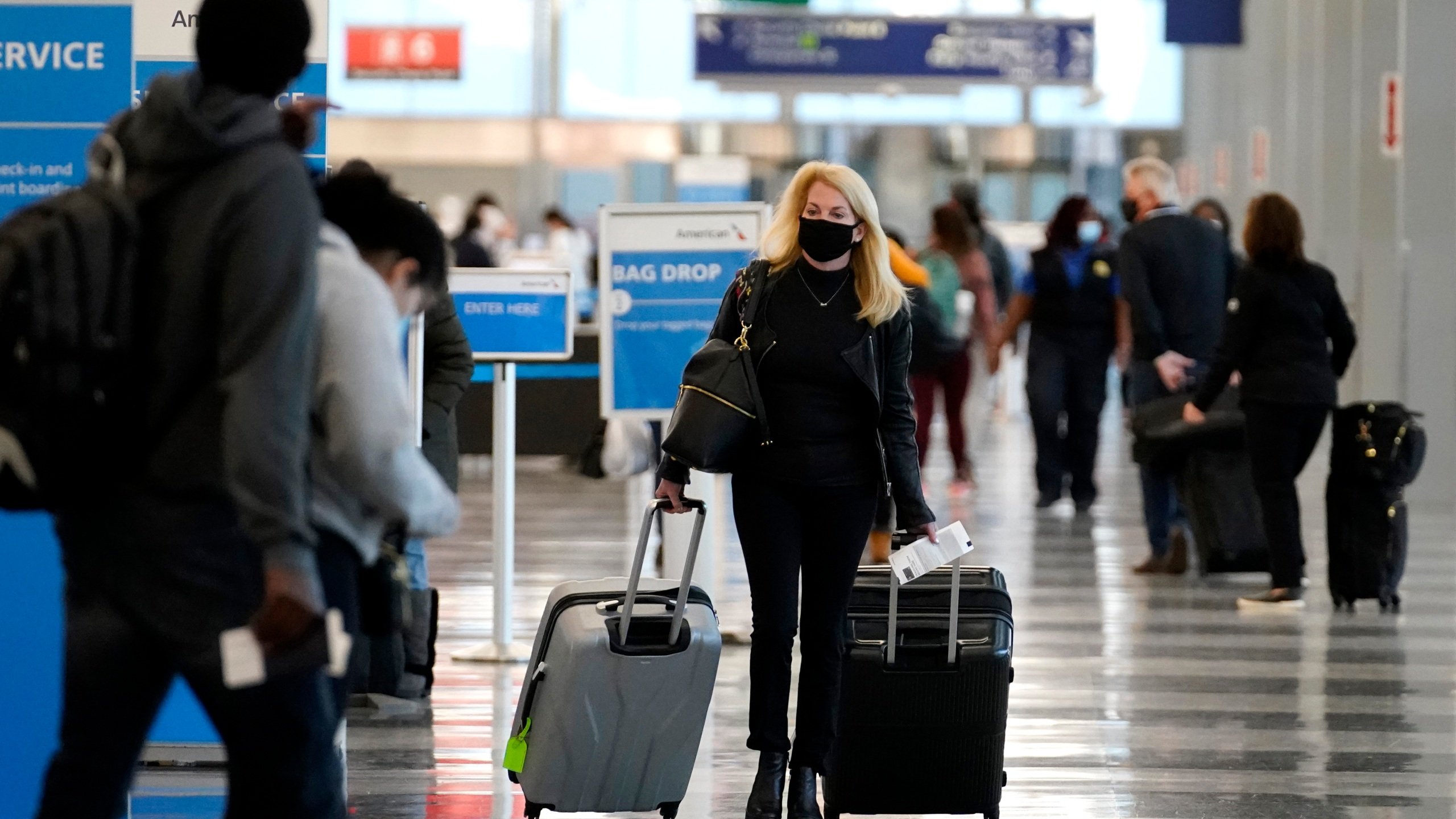 In this Sunday, Nov. 29, 2020 file photo, a traveler wears a mask as she walks through Terminal 3 at O'Hare International Airport in Chicago. (AP Photo/Nam Y. Huh, File)