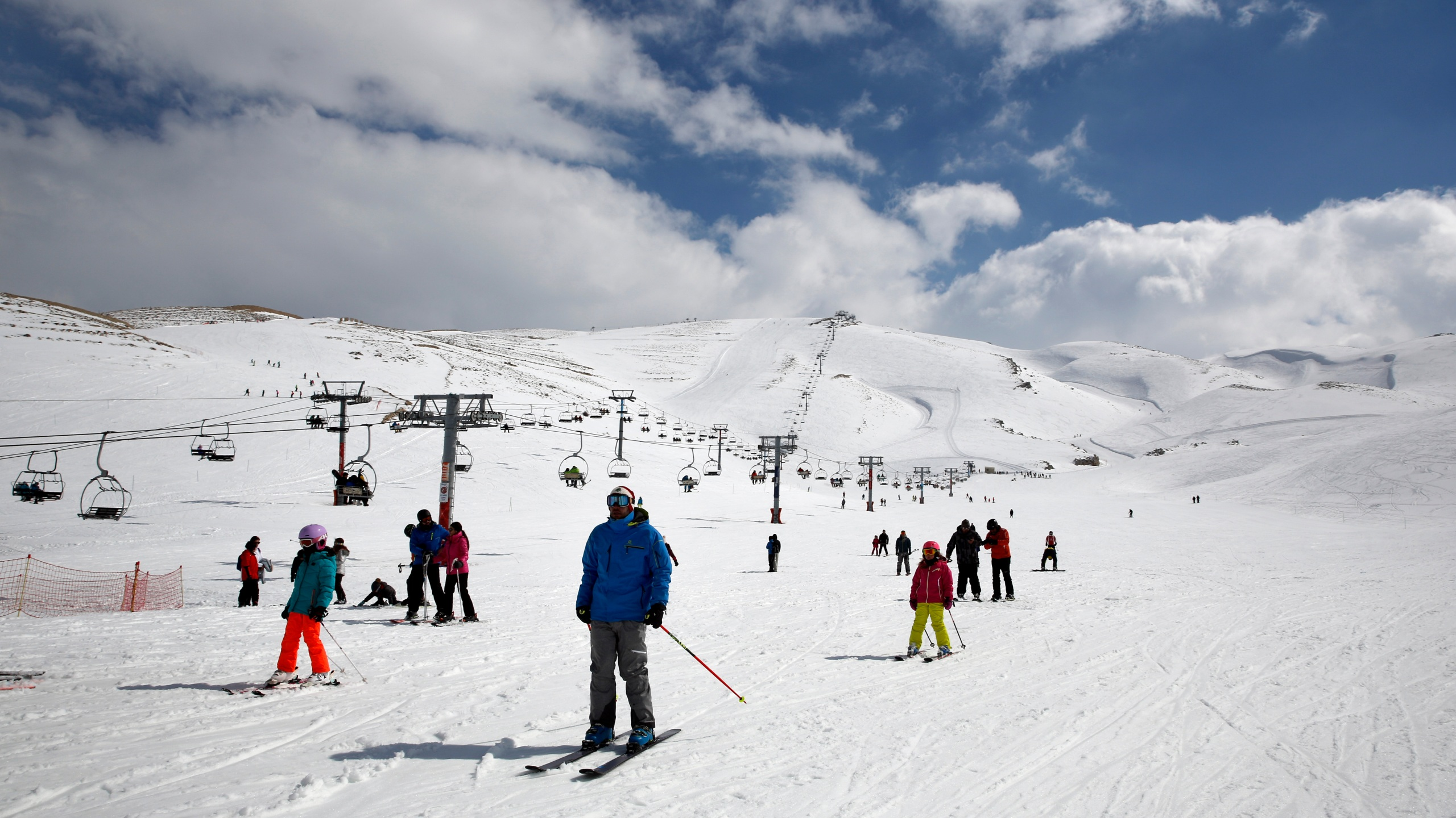 In this Feb. 22, 2019, file photo, people ride lifts as other skiers slide down the hill on a sunny day at the Faraya-Mzaar ski resort, in Faraya, northeast of Beirut, Lebanon. (Bilal Hussein / Associated Press)
