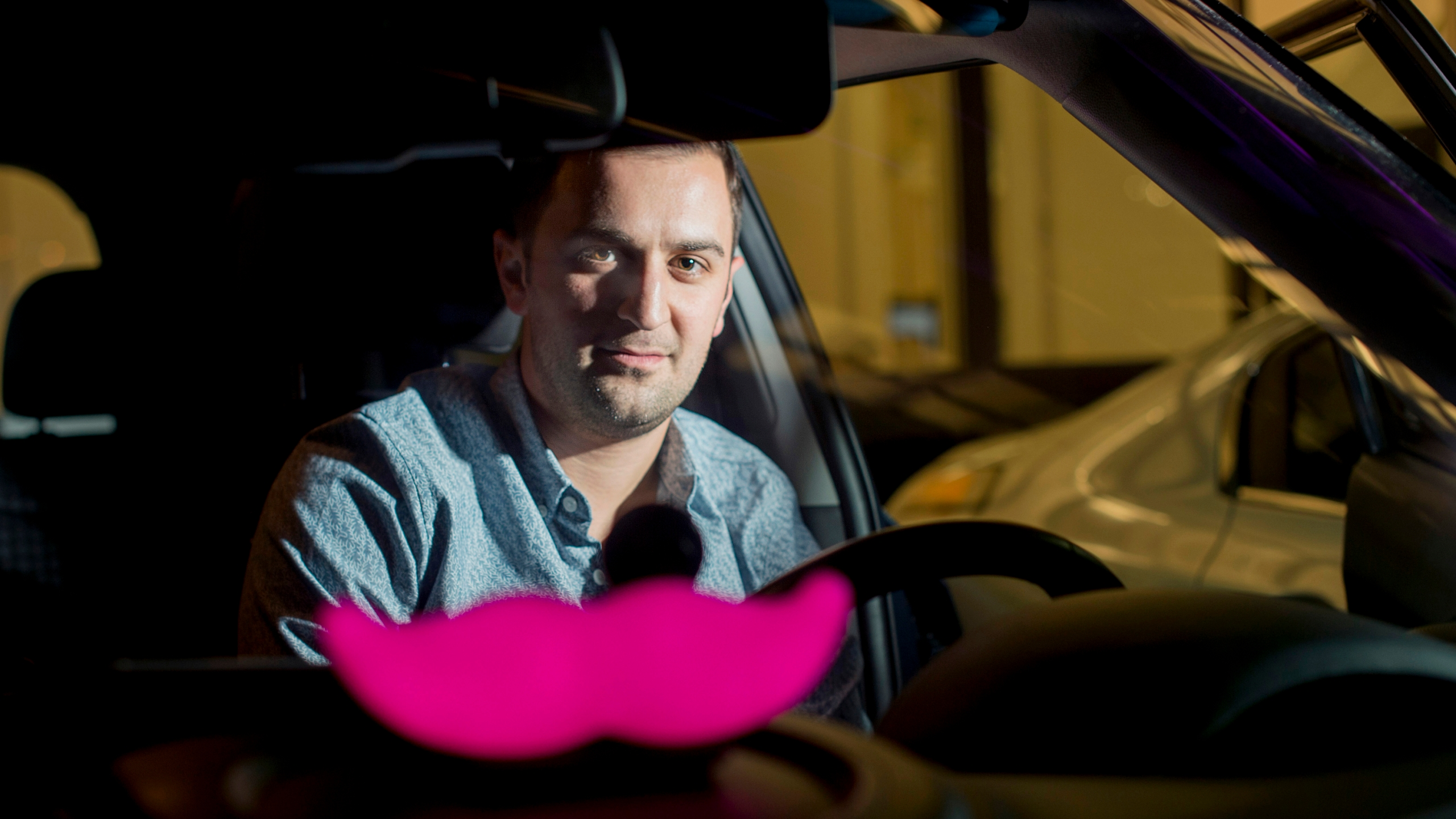 "In this Jan. 26, 2015, file photo, Lyft co-founder John Zimmer displays his company's ""glowstache"" following a launch event in San Francisco. (Noah Berger/Associated Press)"