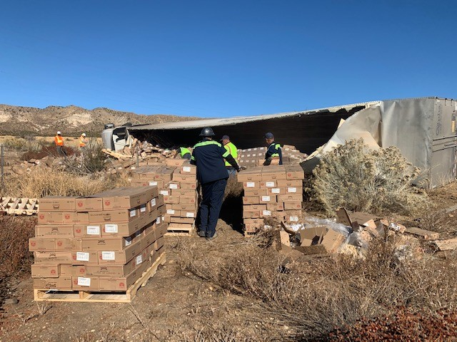 Caltrans crews help clean up the dozens of boxes of cookie dough alongside the Cajon Pass on Thursday. (Caltrans via Twitter)