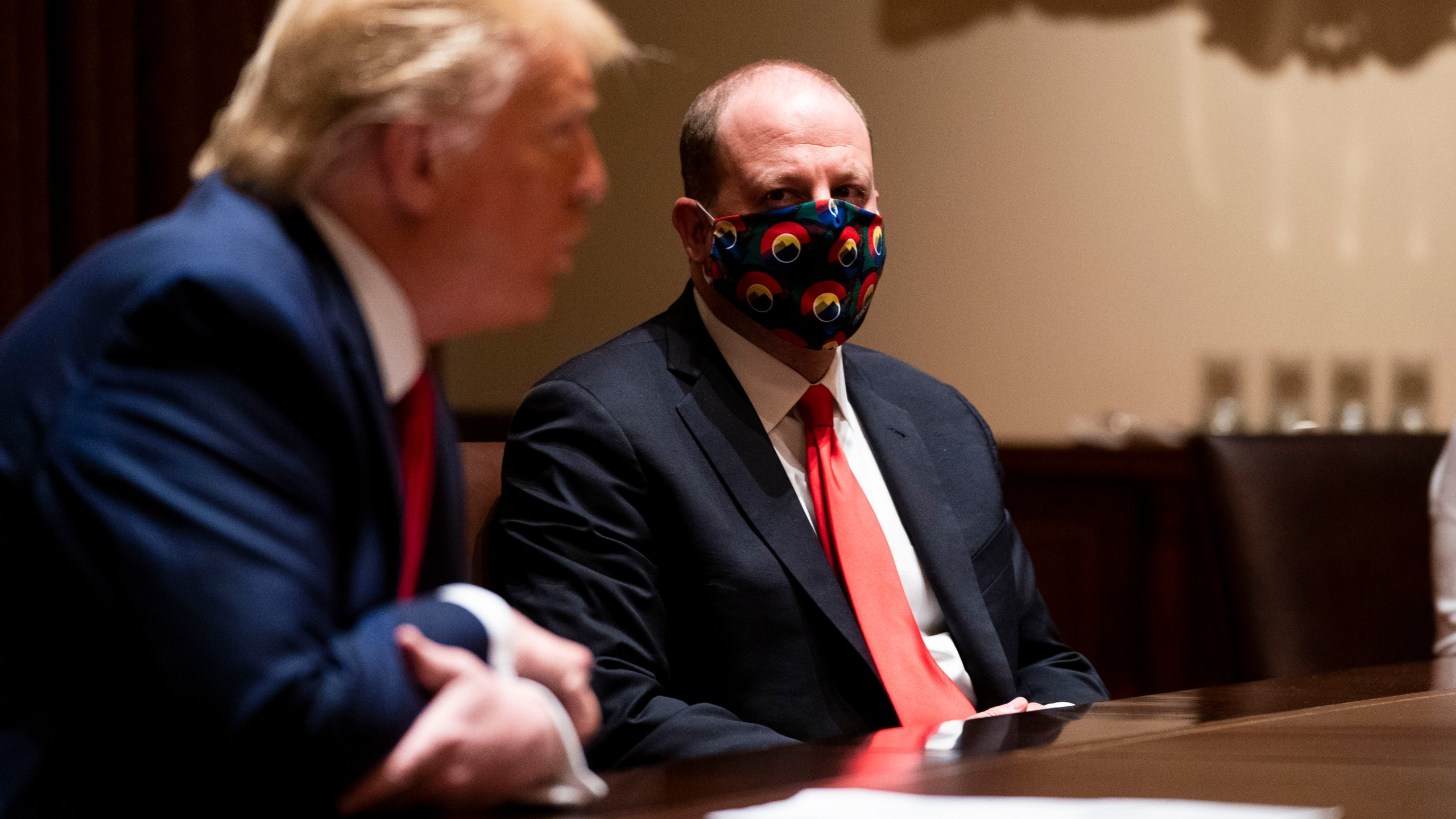 Colorado Governor Jared Polis wears a face mask as U.S. President Donald Trump makes remarks during a meeting in the Cabinet Room of the White House, May 13, 2020 in Washington, DC. (Photo by Doug Mills-Pool/Getty Images)