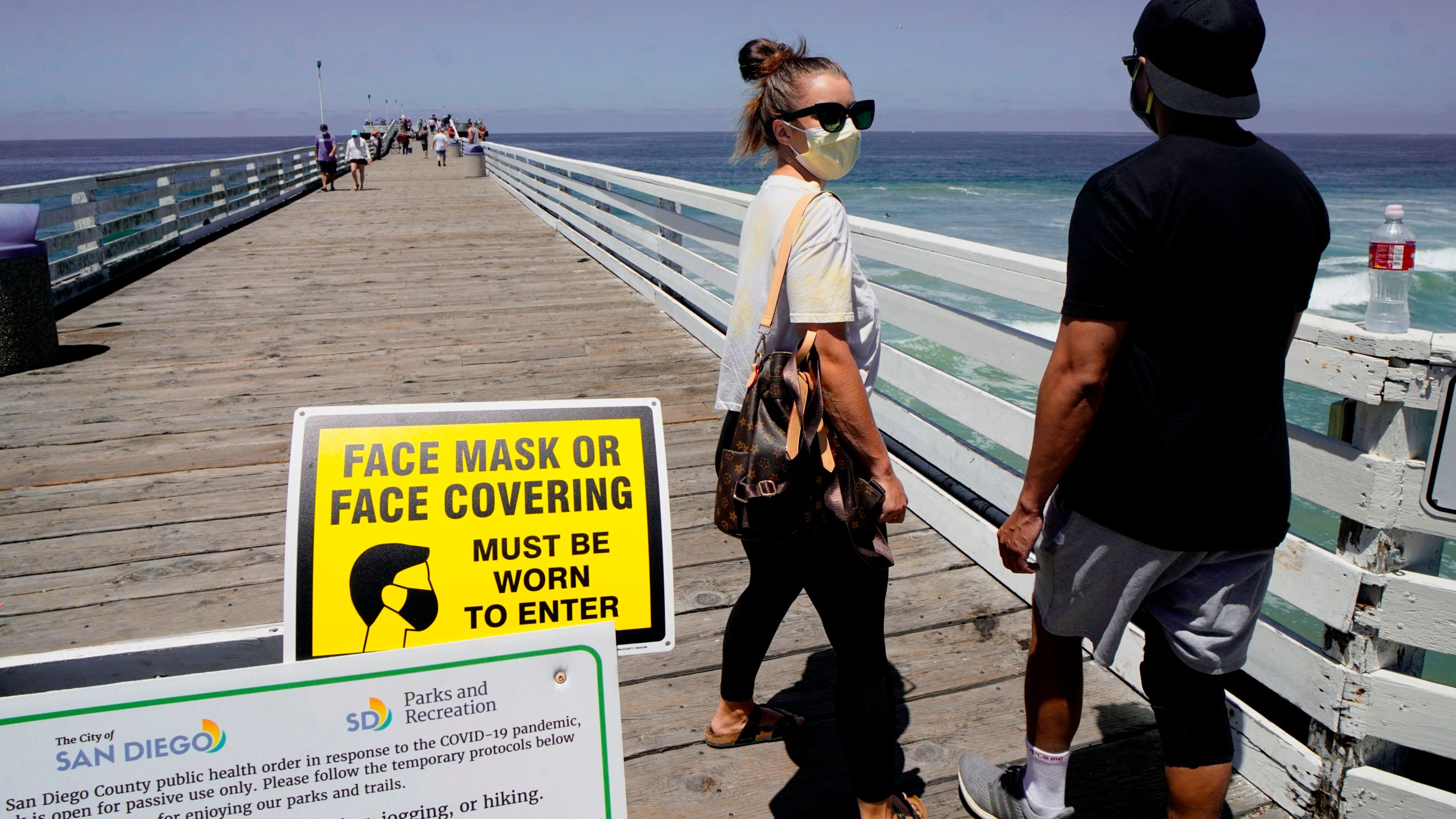 Beachgoers walk out onto the Pacific Beach Pier in San Diego on Saturday, July 4, 2020, amid the coronavirus pandemic. (SANDY HUFFAKER/AFP via Getty Images)