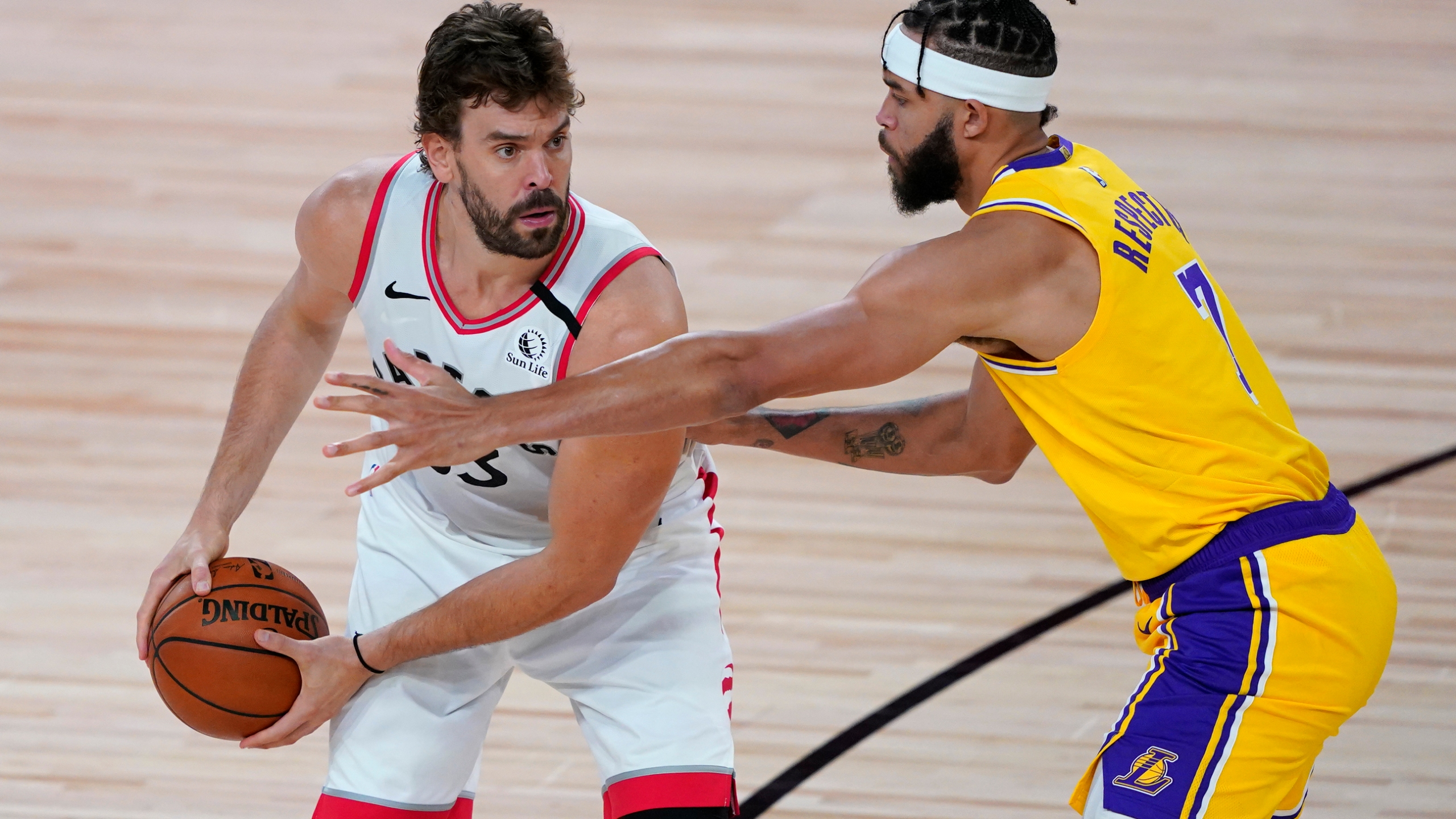 Marc Gasol holds the ball against JaVale McGee during the second half of an NBA basketball game between the Toronto Raptors and the L.A. Lakers at The Arena in the ESPN Wide World Of Sports Complex on Aug. 1, 2020 in Lake Buena Vista, Florida. (Ashley Landis - Pool/Getty Images)