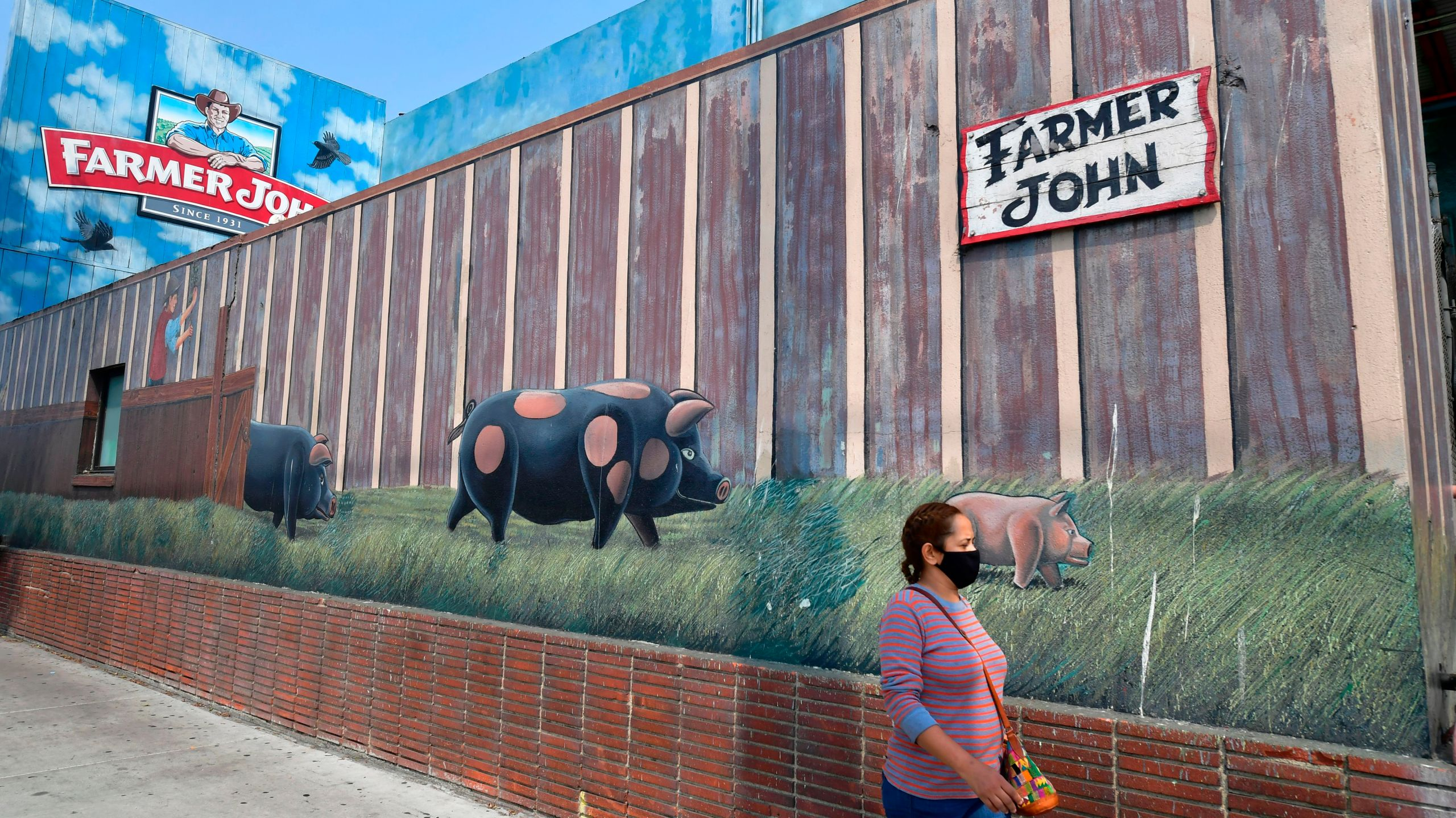 In this Sept. 14, 2020, photo, a woman wears a facemask while walking past the Farmer John plant in Vernon, which was hit with a safety fine after an outbreak of hundreds of coronavirus cases. (Frederic J. Brown / AFP / Getty Images)