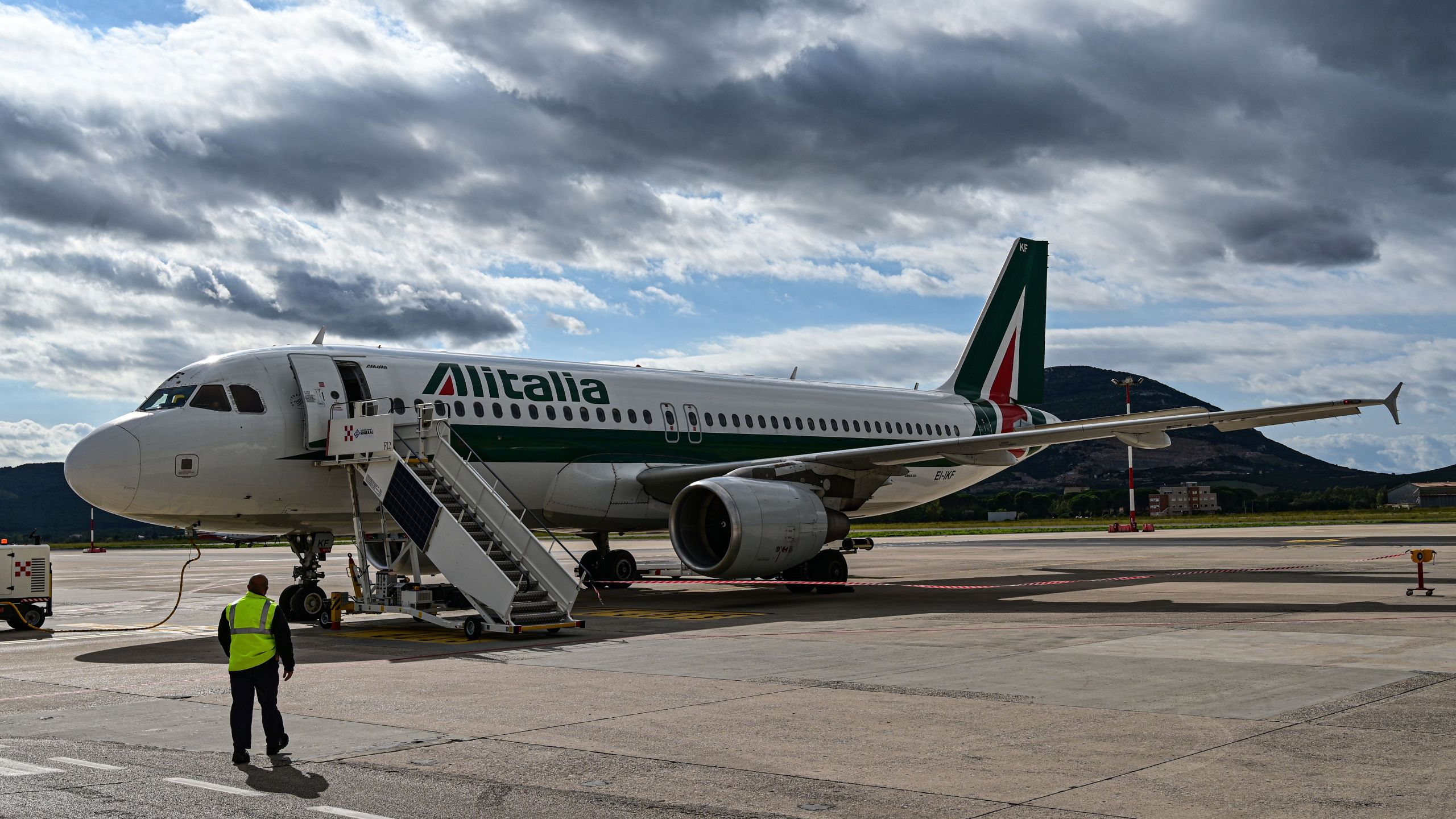 "An airport employee walks towards an Alitalia plane just arrived at the Alghero-Fertilia ""Riviera del Corallo"" Airport on October 6, 2020. (Miguel Medina/AFP via Getty Images)"