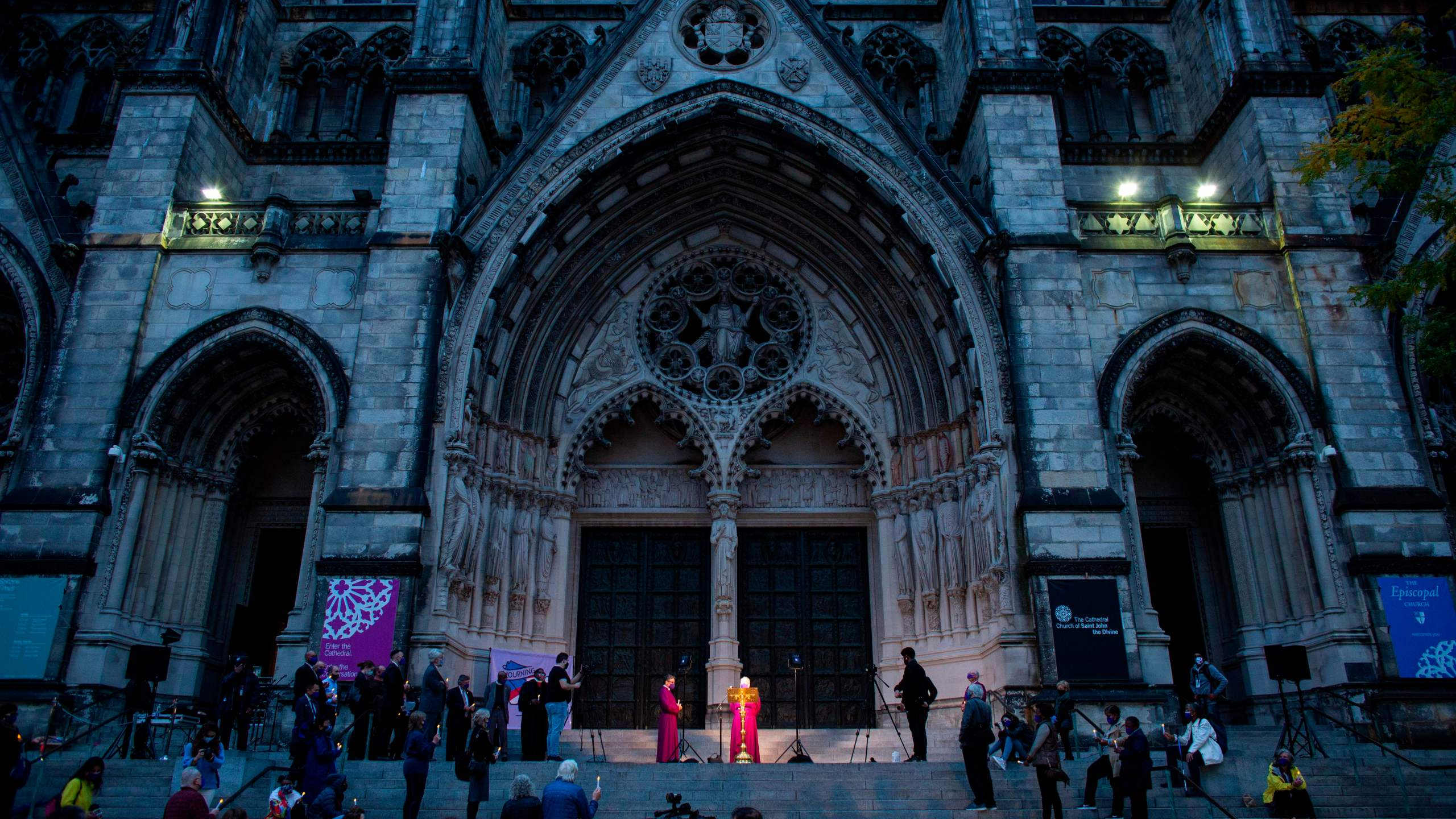 People attend a candlelight vigil a procession in tribute to all of the lives affected by the novel coronavirus outside The Cathedral of St. John the Divine in New York City on Oct. 19, 2020. (Kena Betancur / AFP / Getty Images)