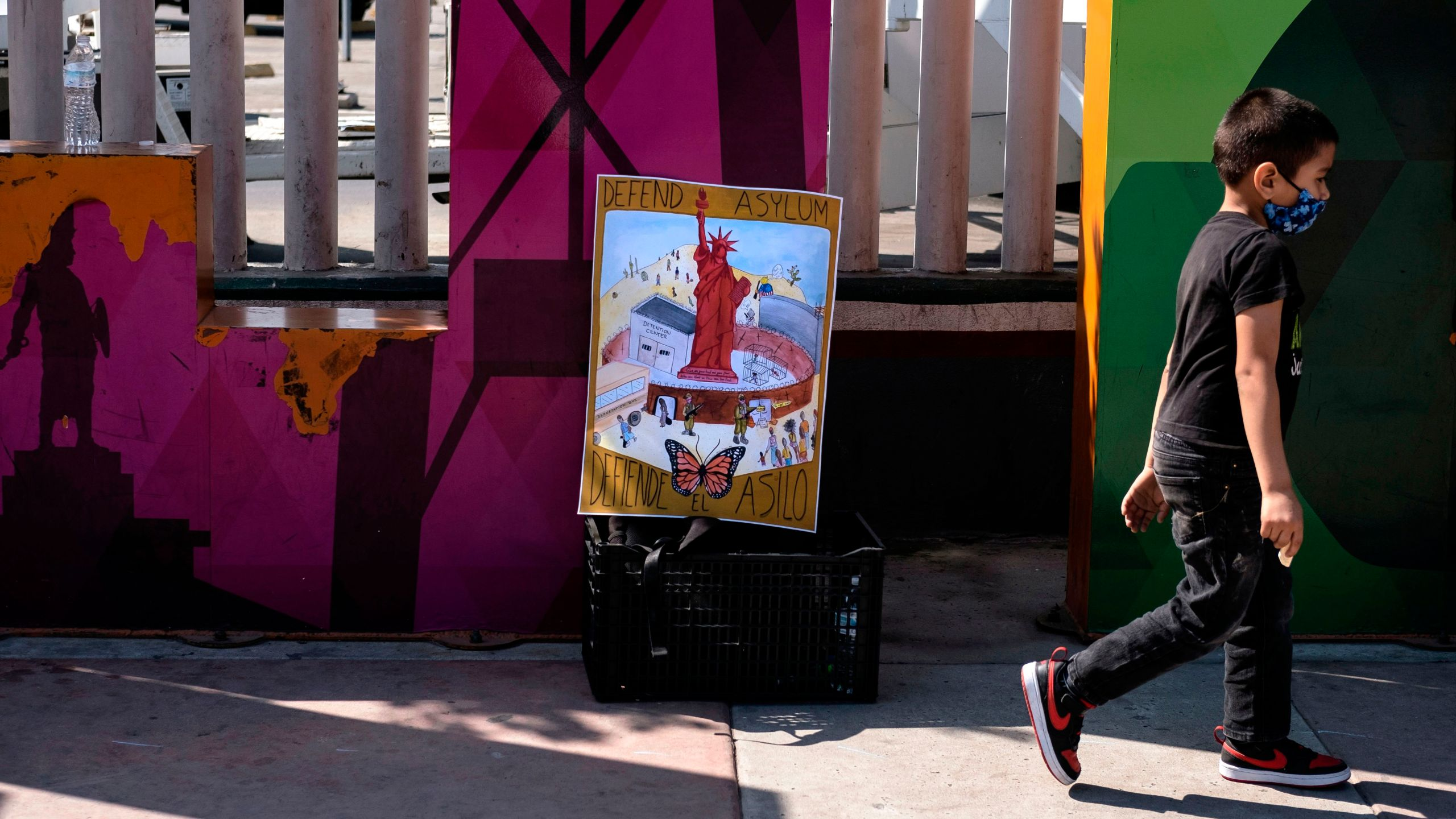 A child takes part in a protest of migrants and human rights activists against U.S. and Mexican migration policies at the San Ysidro crossing port, in Tijuana, Baja California state, Mexico, on the border with the U.S., on Oct. 21, 2020, amid the new coronavirus pandemic. (GUILLERMO ARIAS/AFP via Getty Images)