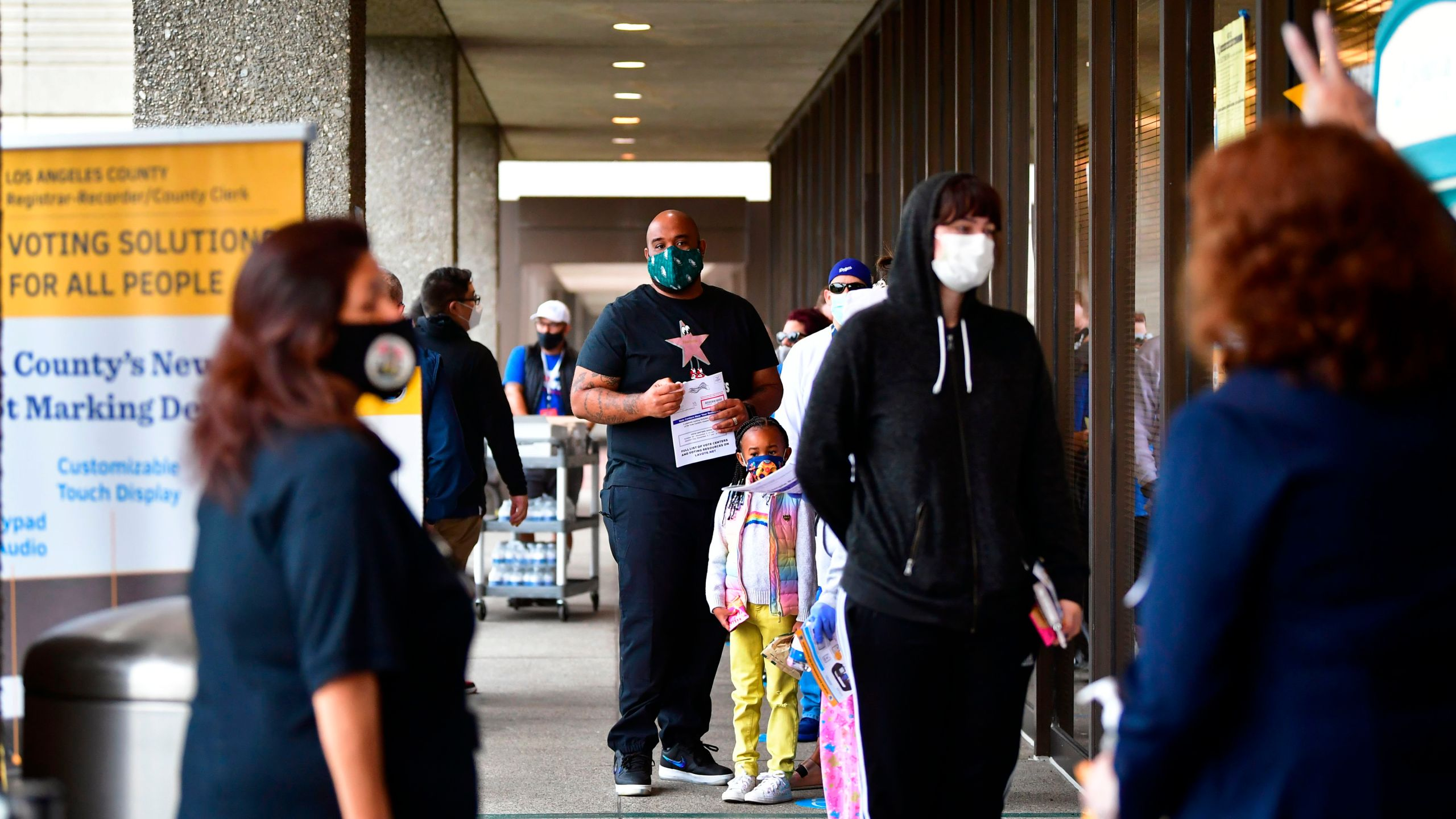 Voters wear face-coverings while waiting in line to vote for the 2020 US elections at the Los Angeles County Registrar in Norwalk on Nov. 3, 2020. (Frederic J. Brown / AFP / Getty Images)