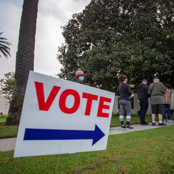 People stand in line to vote as the sun rises the Main Street Branch Library vote center on Nov. 3, 2020, in Huntington Beach, California. (Apu Gomes/Getty Images)