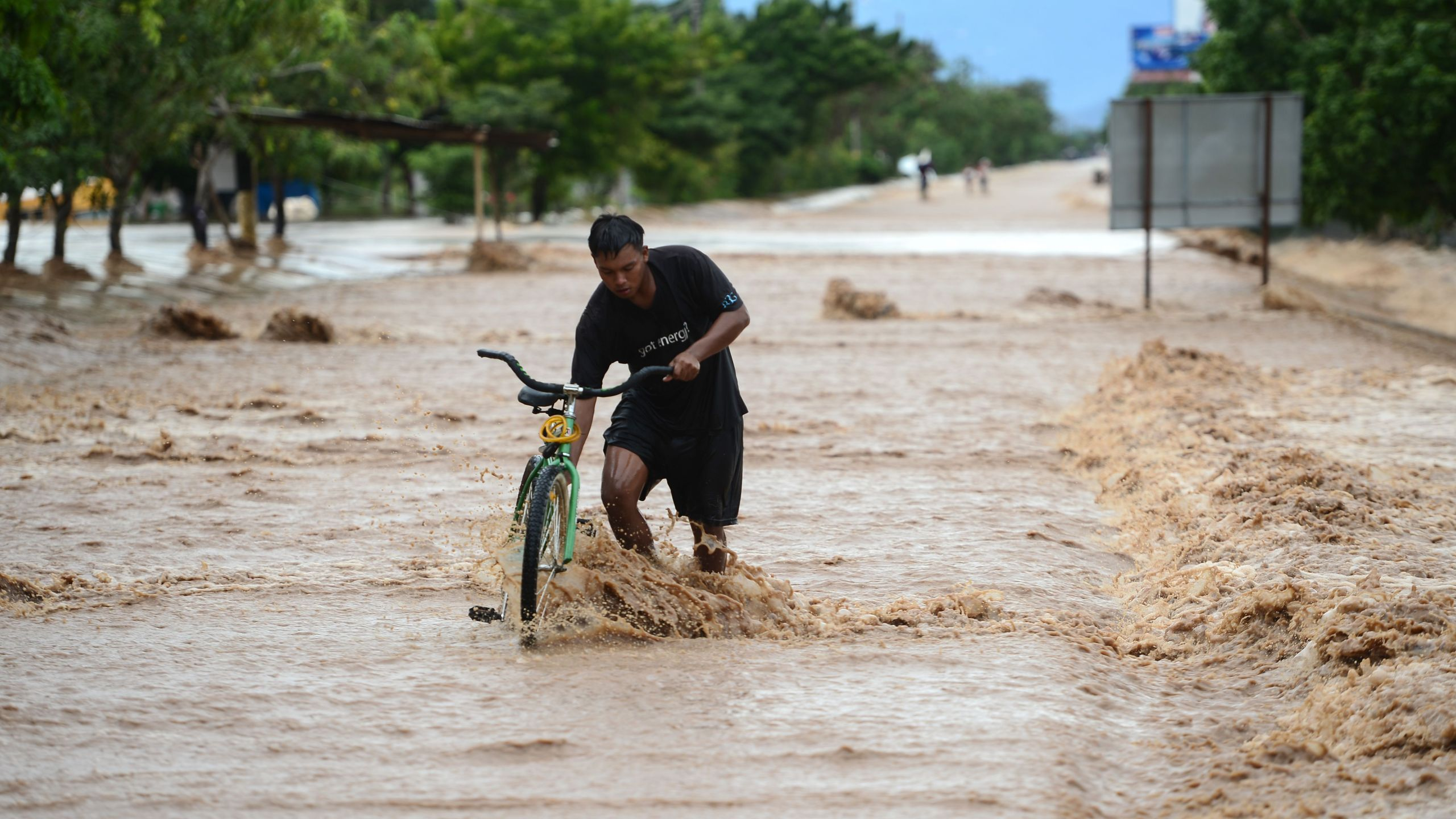 A man wades with his bike in a flooded street due to the heavy rains caused by Hurricane Eta, now degraded to a tropical storm, in El Progreso, department of Yoro, 260 kms north of Tegucigalpa, on Nov. 5, 2020. (Orlando SIERRA / AFP via Getty Images)