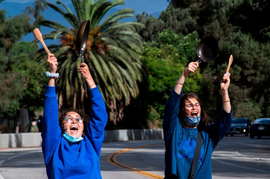 Los Angeles residents Emma Silvers and Hadley Rosenbaum bang pans as they run around the Silverlake reservoir to celebrate Joe Biden being declared the next U.S. President on Nov. 7, 2020. (ROBYN BECK/AFP via Getty Images)