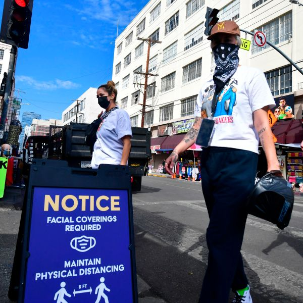 A signboard reminds people of the face covering requirement as pedestrians wear face masks due to the coronavirus in Los Angeles on Nov. 12, 2020. (FREDERIC J. BROWN/AFP via Getty Images)