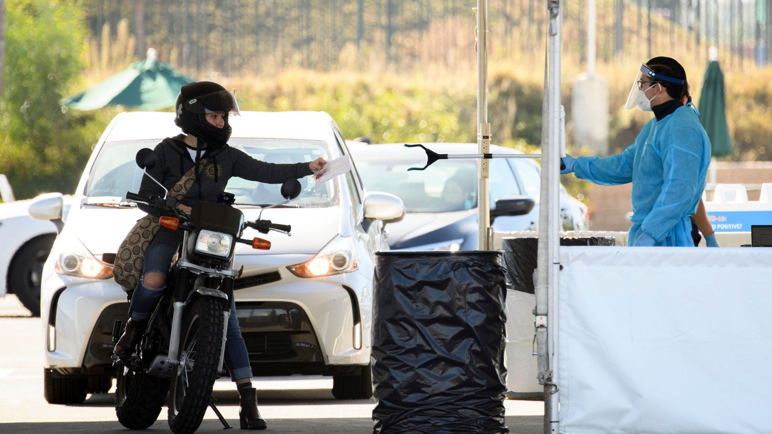 A COVID-19 testing site staff member uses a tool to collect paperwork from a motorcyclist at a drive-up testing site at the Orange County Fairgrounds in Costa Mesa, California, on Nov. 17, 2020. (PATRICK T. FALLON/AFP via Getty Images)