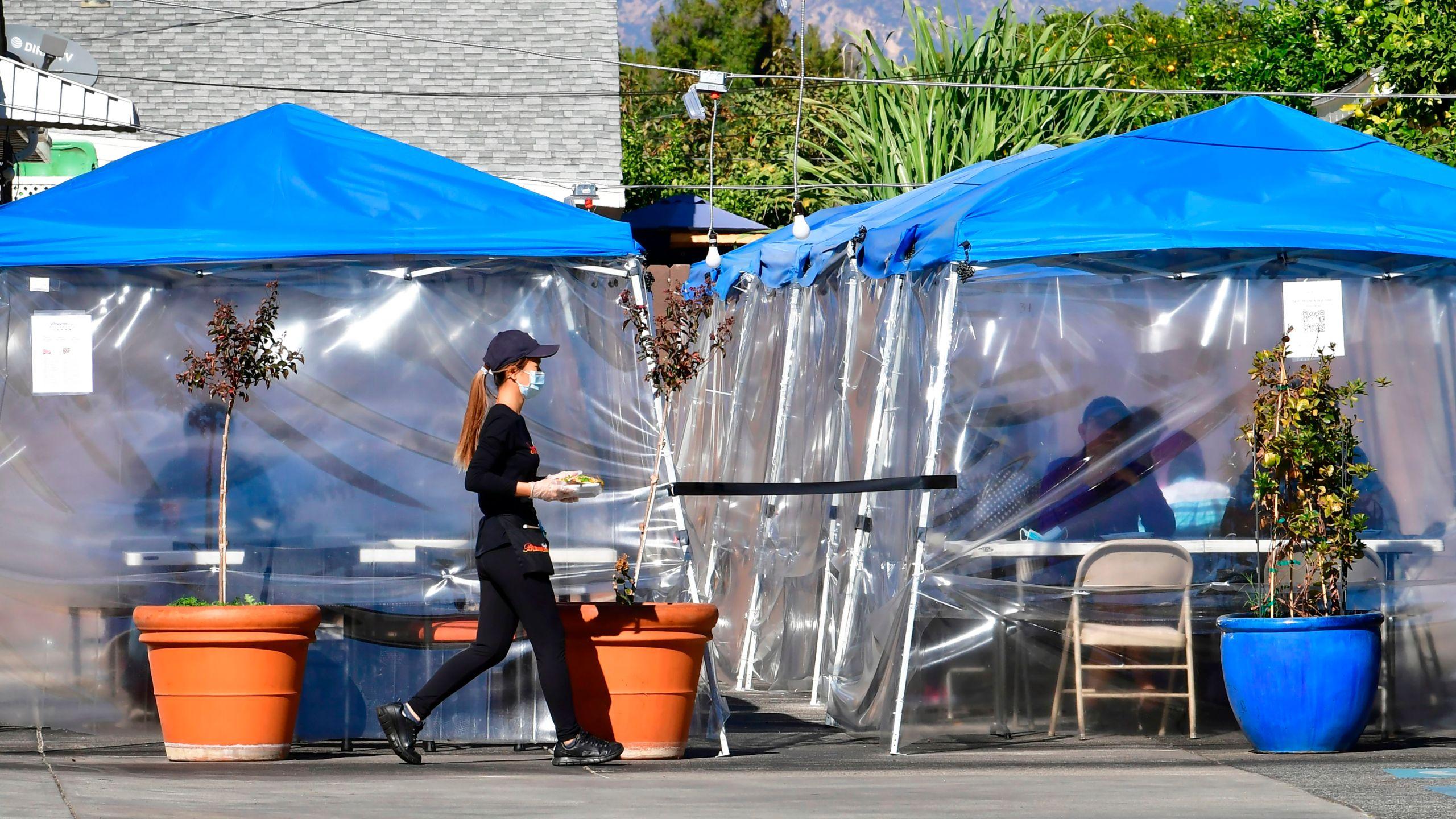 2020年11月17日,在阿罕布拉市一家餐厅的停车场,一名女服务员为坐在户外帐篷下的食客送餐。(FREDERIC J. BROWN/AFP via Getty Images)(photo:KTLA)