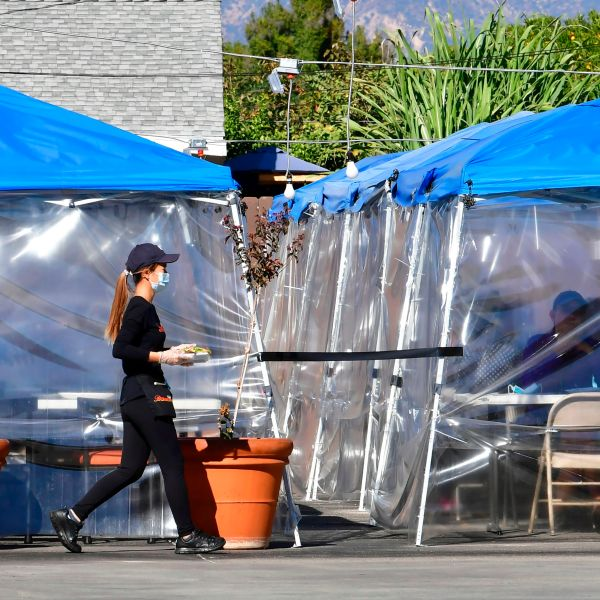 A waitress delivers orders to diners seated outdoors under tents in a restaurant's parking lot on Nov. 17, 2020 in Alhambra. (FREDERIC J. BROWN/AFP via Getty Images)