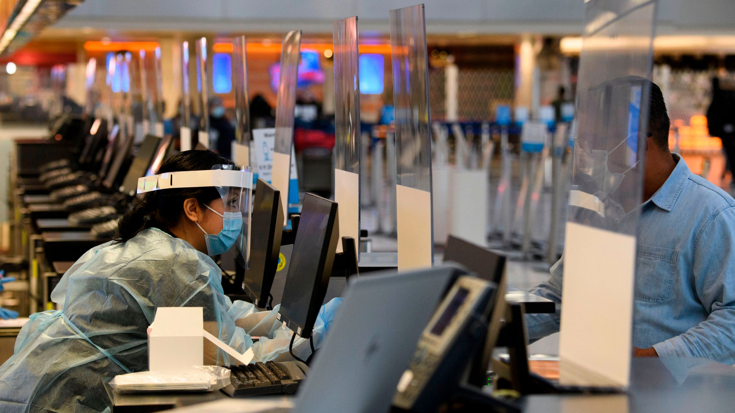 A staff member wears personal protective equipment while talking with a traveler at an coronavirus testing location at the Tom Bradley International Terminal at LAX on Nov. 18, 2020.(Patrick FALLON/AFP via Getty Images)