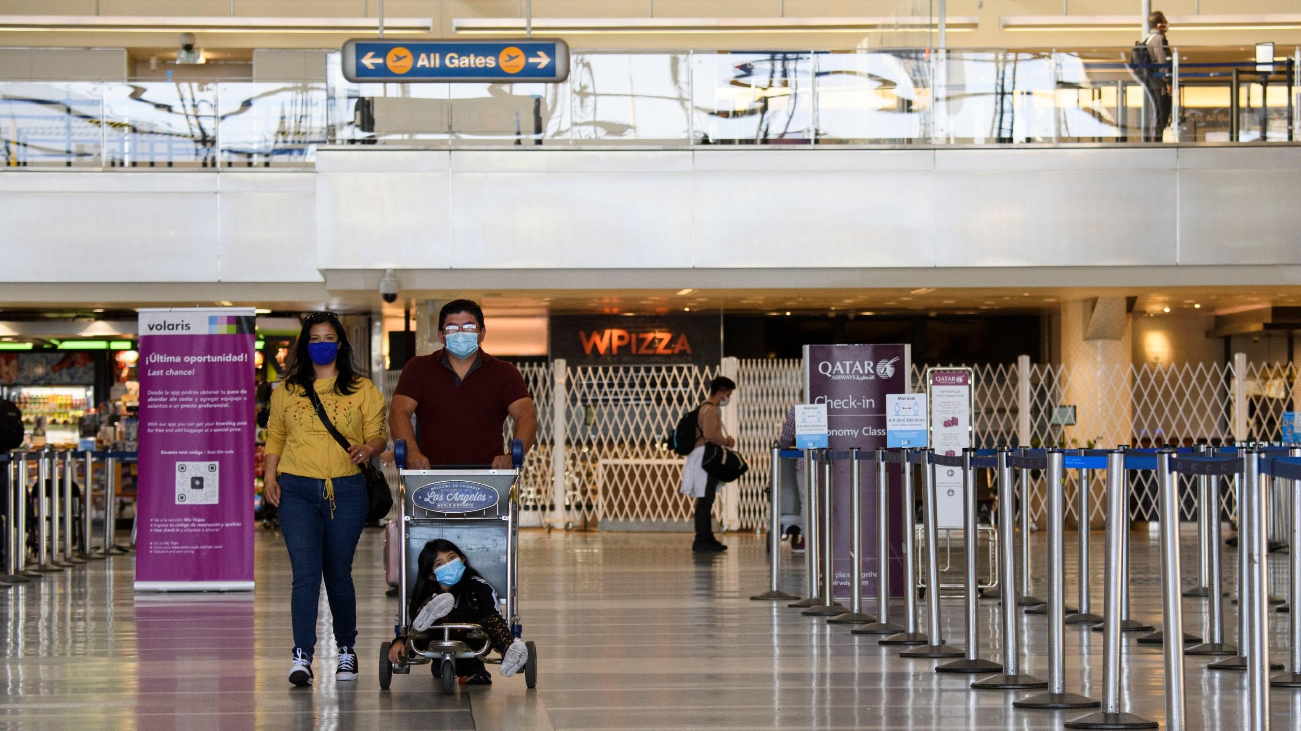 Travelers walk past flight check-in counters inside the Tom Bradley international Terminal at Los Angeles International Airport (LAX) in Los Angeles, California, Nov. 18, 2020. (PATRICK FALLON/AFP via Getty Images)