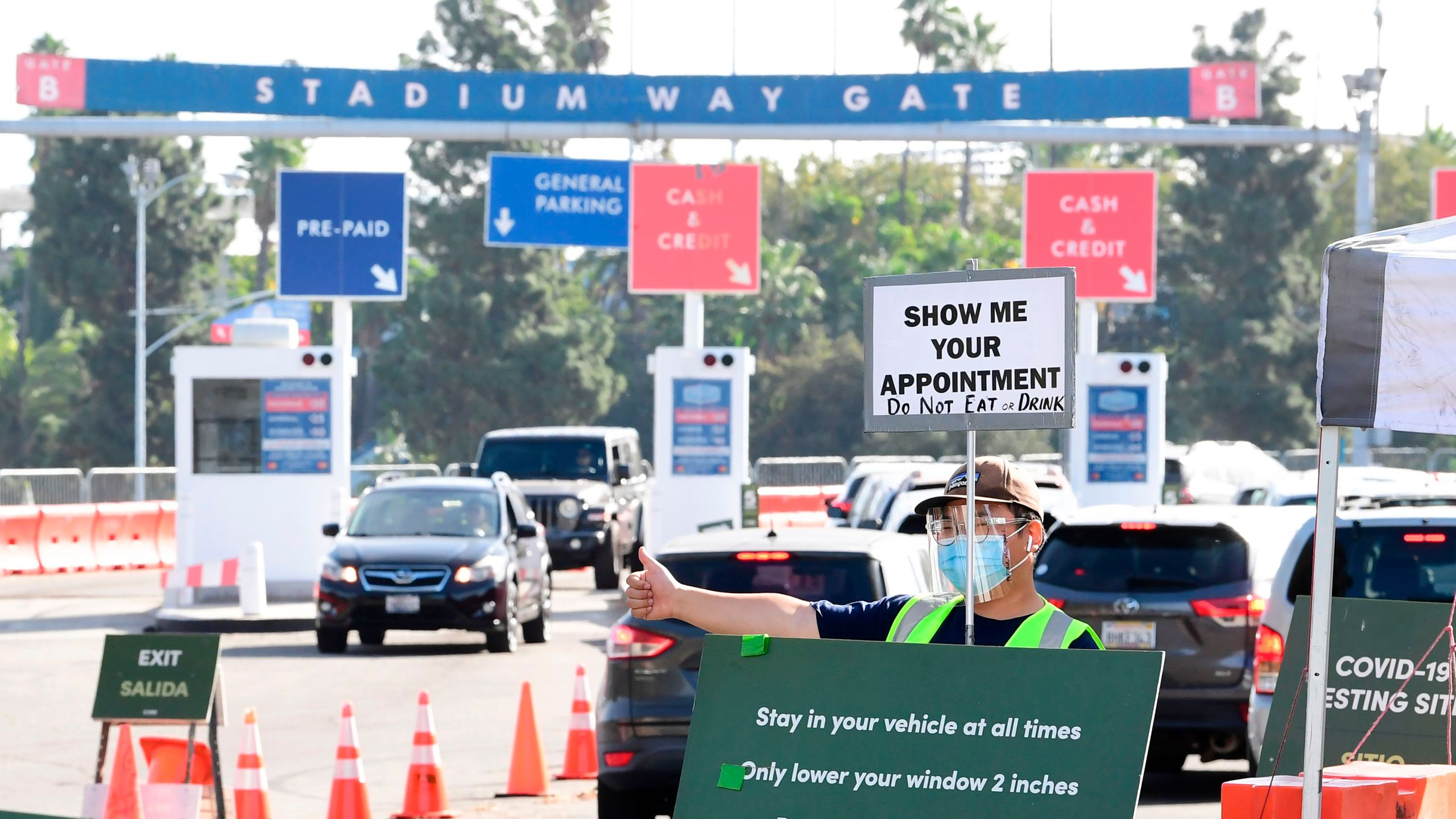 A Testing Center worker checks for appointments from drivers arriving at Dodger Stadium for Covid-19 testing on November 20, 2020 in Los Angeles, California. (Frederic J. Brown/AFP via Getty Images)