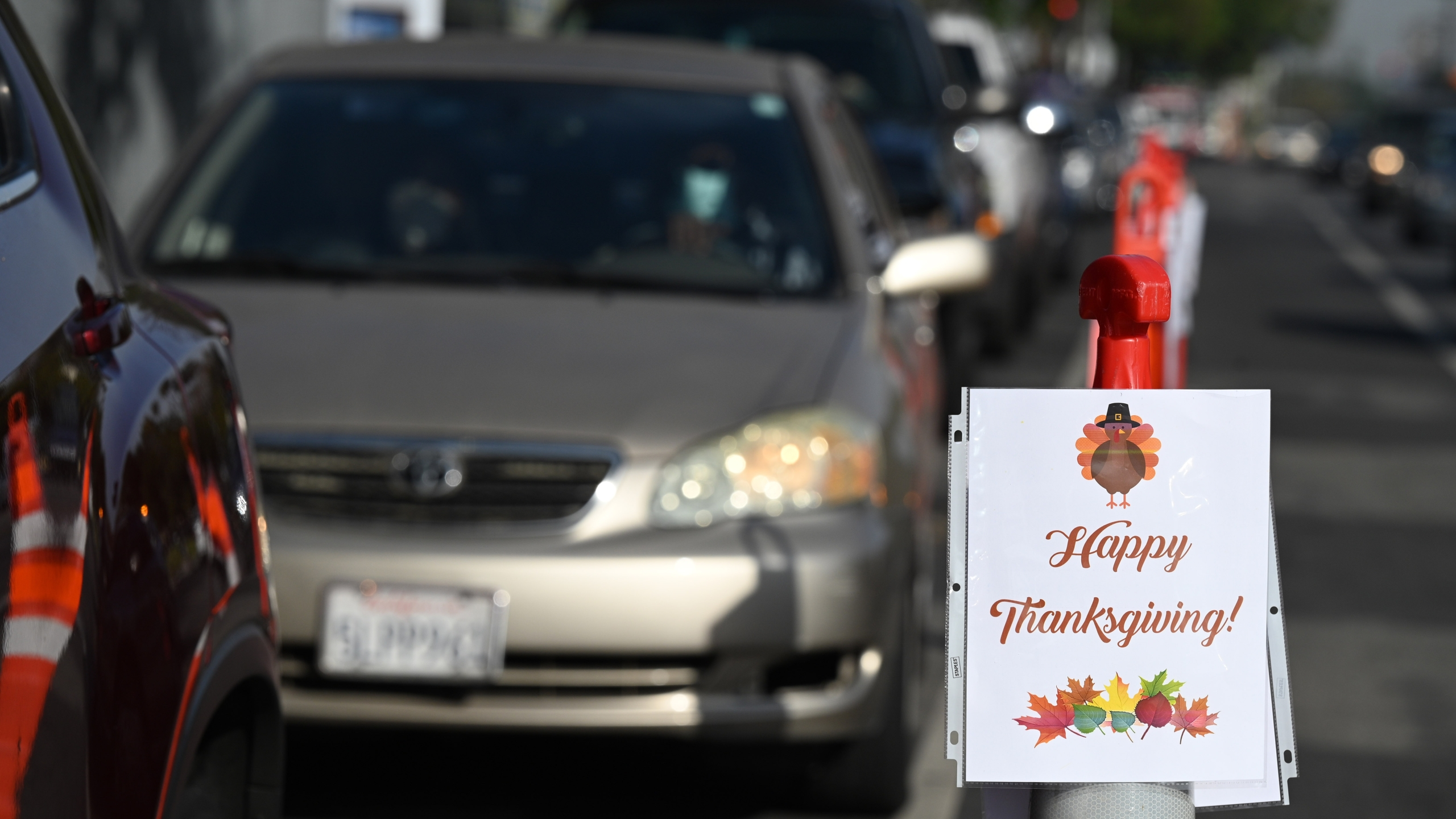 Local residents who have been financially impacted by the coronavirus COVID-19 pandemic wait in line in their cars for a Thanksgiving meal take home kit at a food distribution organized by the L.A. Mission, Nov. 20, 2020, outside Compton Avenue Elementary School in Los Angeles. (ROBYN BECK/AFP via Getty Images)