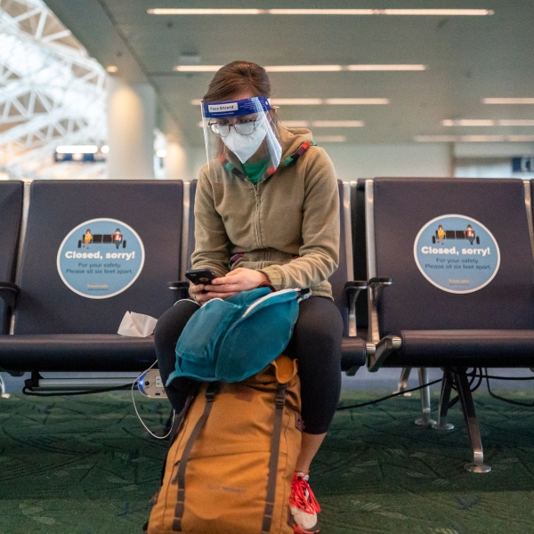 A traveler checks their phone while waiting for a flight at Portland International Airport on Nov. 25, 2020. (Nathan Howard / Getty Images)