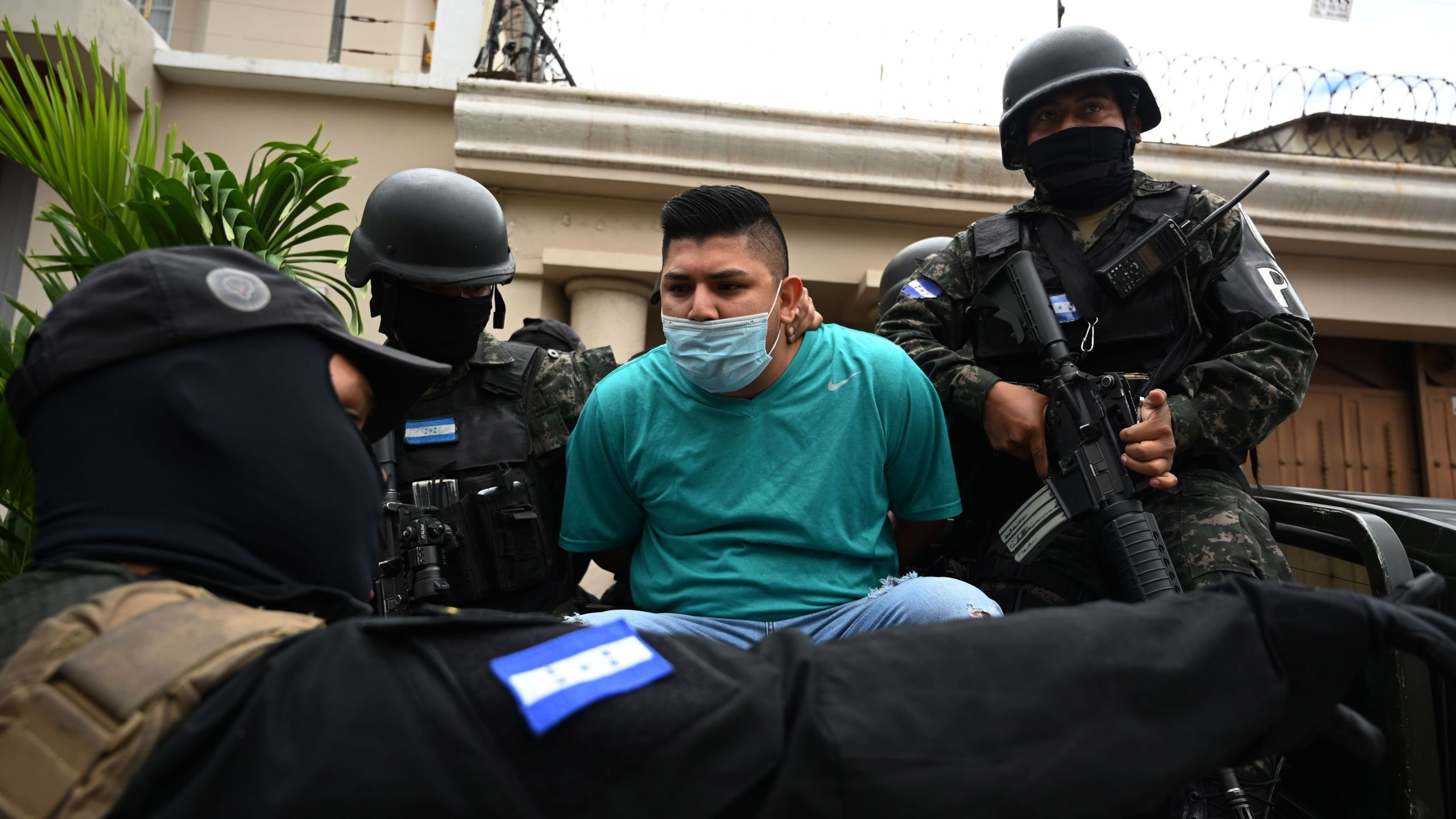 Members of the National Anti Maras and Gangs Force (FNAMP) arrest Jose Alejandro Nunez Cruz (C), alleged administrator of the criminal gang Mara Salvatrucha 13 (MS-13), at an exclusive residential area in Tegucigalpa, on November 26, 2020. (Orlando Sierra/AFP via Getty Images)