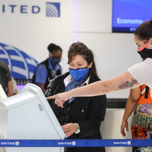 A United Airlines employee wears a required face covering along with a passenger at check-in at Los Angeles International Airport on Oct. 1, 2020 in Los Angeles. (Mario Tama/Getty Images)