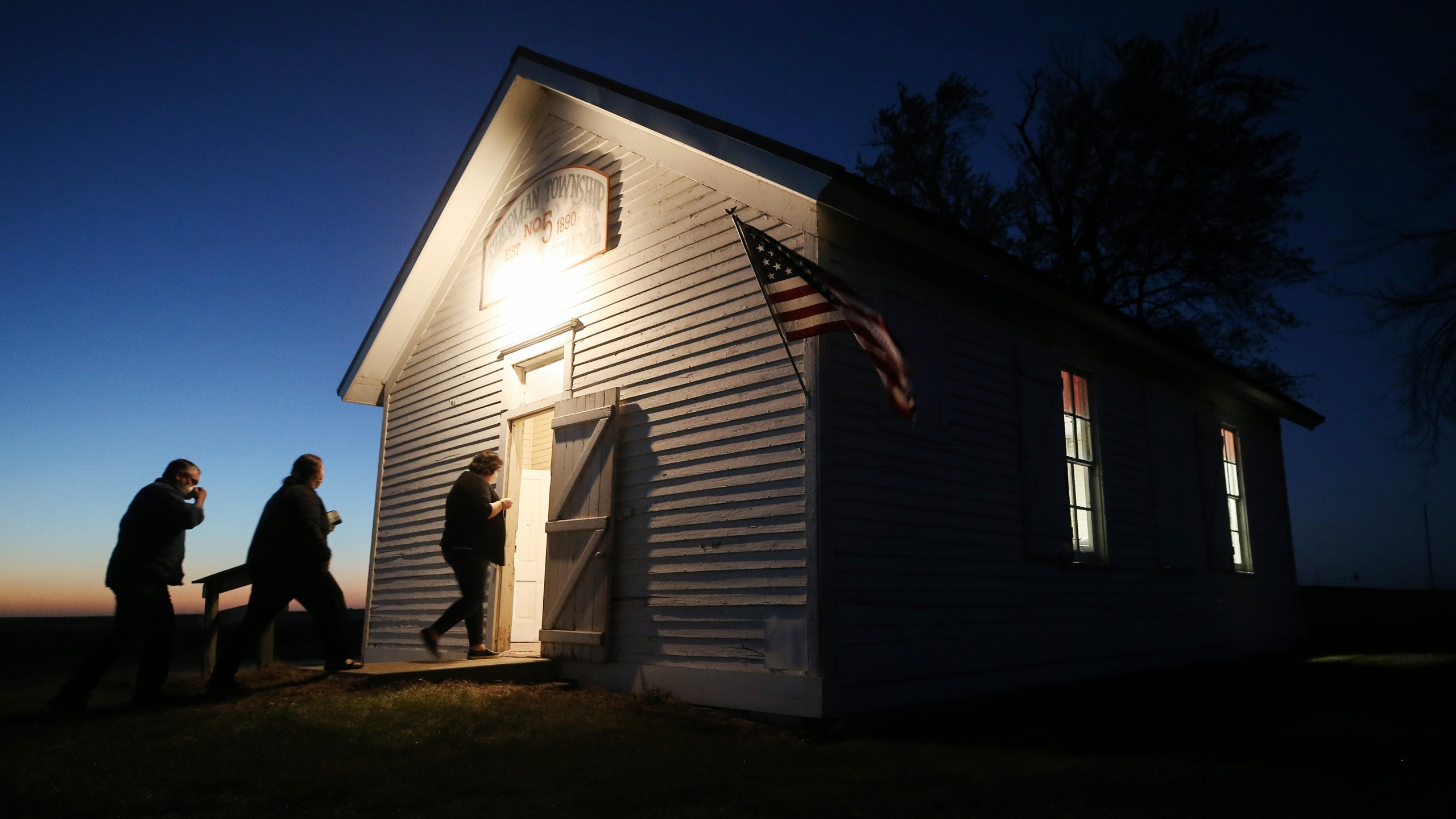 Voters enter a polling place at dusk to cast their ballots at Sherman Township Hall, a former one room schoolhouse in Zearing, Iowa, on Nov. 3, 2020. (Mario Tama / Getty Images)