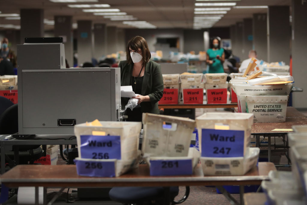 Claire Woodall-Vogg, executive director of the Milwaukee election commission, collects the count from absentee ballots from a voting machine on November 04, 2020 in Milwaukee. Wisconsin requires election officials to wait to begin counting absentee ballots until after polls open on election day.(Scott Olson/Getty Images)