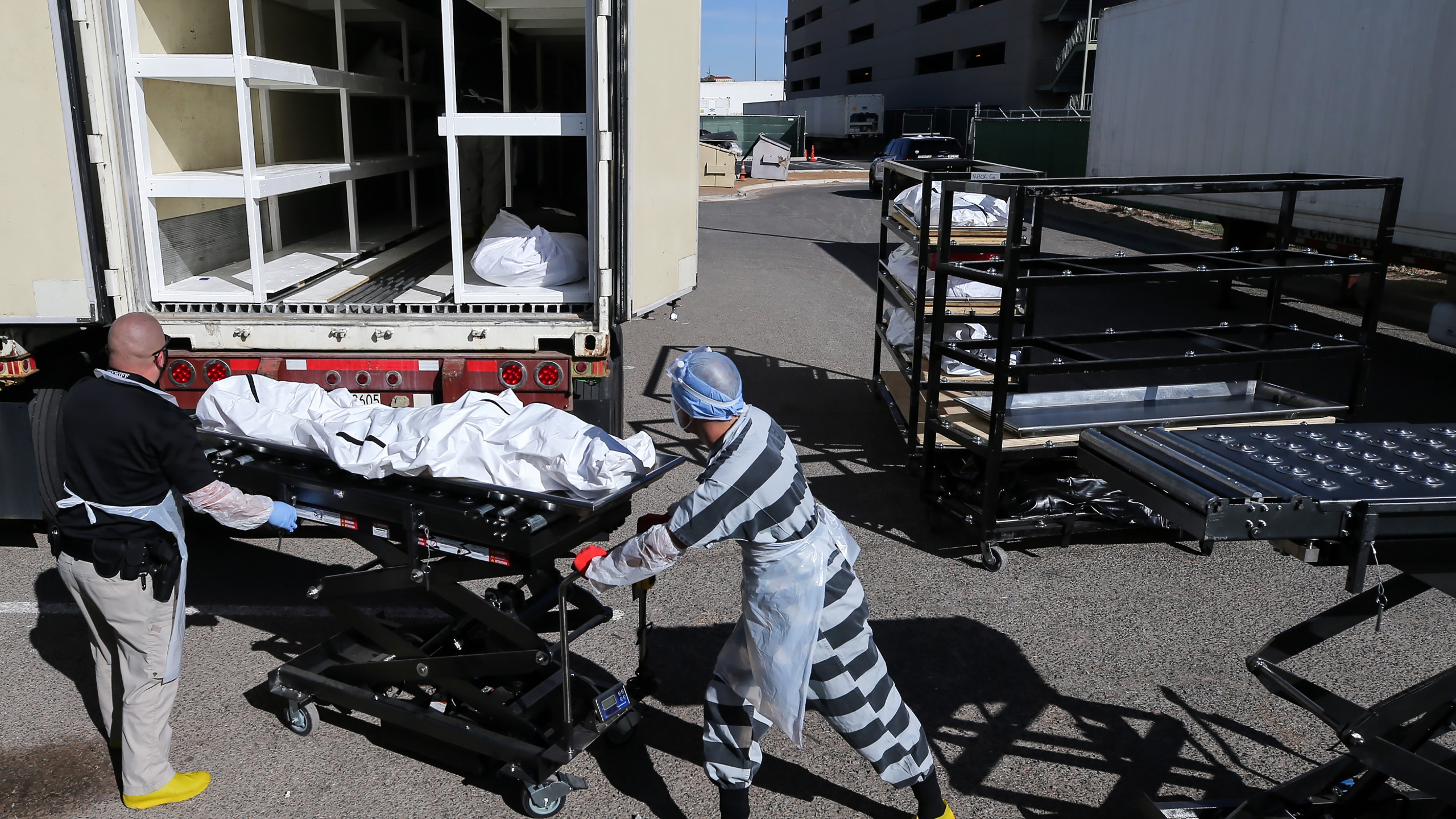 An inmate from El Paso County detention facility works while loading bodies wrapped in plastic into a refrigerated temporary morgue trailer in a parking lot of the El Paso County Medical Examiner's office on Nov. 17, 2020 in El Paso, Texas. (Mario Tama/Getty Images)