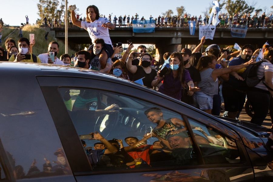 Fans on the side of the highway cheer for the hearse carrying the body of Diego Maradona that transports him through 25 de Mayo Highway to Jardín de Bella Vista before the burial ceremony on Nov. 26, 2020. (Tomas Cuesta / Getty Images)