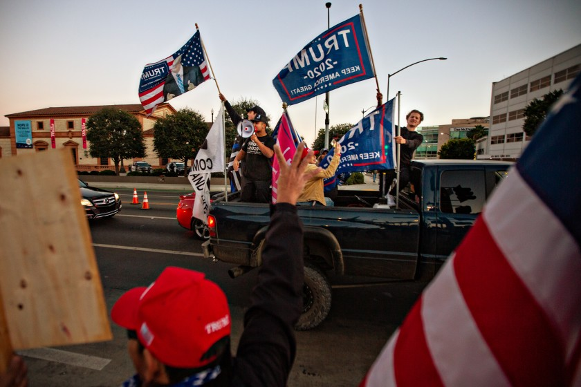 Trump supporters ride in the back of a truck at a rally in Beverly Hills on Nov. 7, 2020, hours after the presidential election was called for Joe Biden. (Jason Armond / Los Angeles Times)