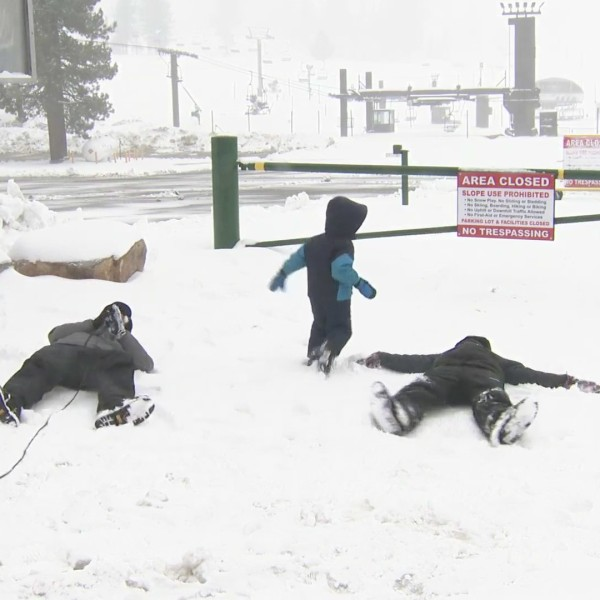 Gene Kang makes a snow angel with a couple of visitors to Big Bear on Nov. 8, 2020. (KTLA)