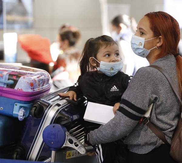 Karen Alvarez and her 3-year-old daughter, Mercedez Gomez, wait in line at the Tom Bradley International Terminal at LAX before their flight to Nicaragua on Monday.(Al Seib / Los Angeles Times)