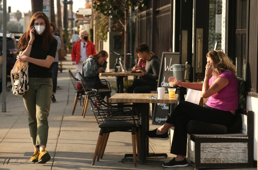 People eat and drink along the sidewalk outside Greenleaf restaurant in Venice on Monday. In a blow to Los Angeles' struggling restaurant and hospitality industry, L.A. County public health officials Sunday announced they will suspend outdoor dining at restaurants amid a surge of new coronavirus cases.(Genaro Molina/Los Angeles Times)