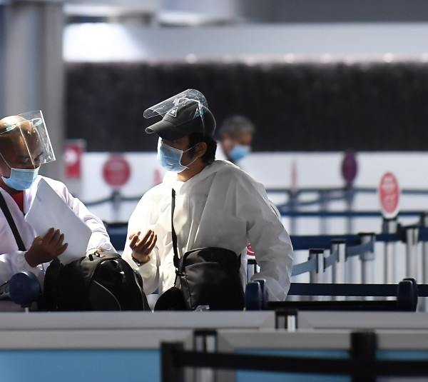 Travelers wearing masks and protective clothing prepare to head to their gate at Terminal 2 at LAX. Gov. Gavin Newsom is urging Californians to restrict travel.(Wally Skalij / Los Angeles Times)