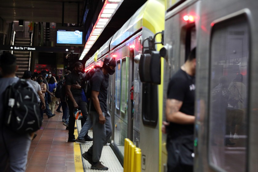 People enter a train at the 7th Street Metro Center in Los Angeles. Los Angeles County residents are urged to stay at home as much as possible as the coronavirus surges.(Dania Maxwell / Los Angeles Times)