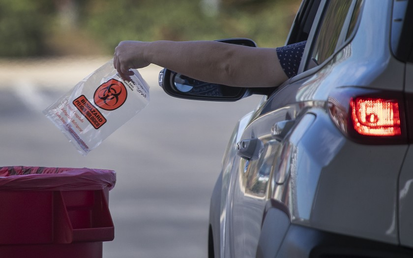 A person deposits a self-administered COVID-19 test at the drive-through testing site at the O.C. Fair & Event Center in Costa Mesa.(Allen J. Schaben / Los Angeles Times)