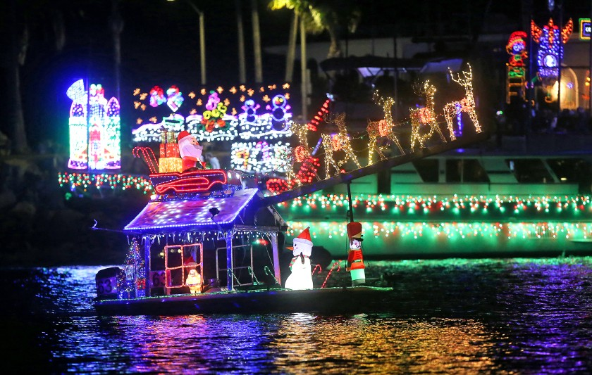 A small boat with a big Santa theme moves along the route during the 111th Newport Beach Christmas Boat Parade in 2019. (Don Leach / Los Angeles Times)