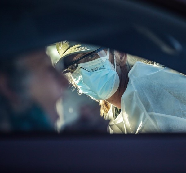 A volunteer watches as a motorist performs a coronavirus nose swab test at Dodger Stadium. (Robert Gauthier / Los Angeles Times)