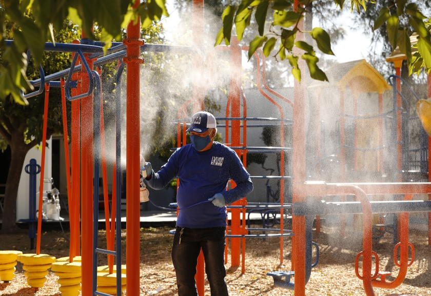 Custodian Carlo Ramos sprays a disinfecting solution on playground equipment at Lupin Hill Elementary School, one of the first L.A. County public schools to open under a special waiver. (Al Seib / Los Angeles Times)